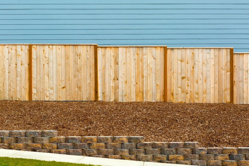 Brick retaining walls on the side of a house, with bark - Ballarat